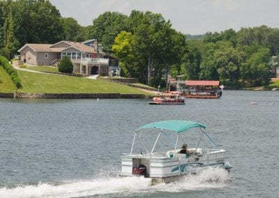 Boat Speeding Past on Lake with House in Distance